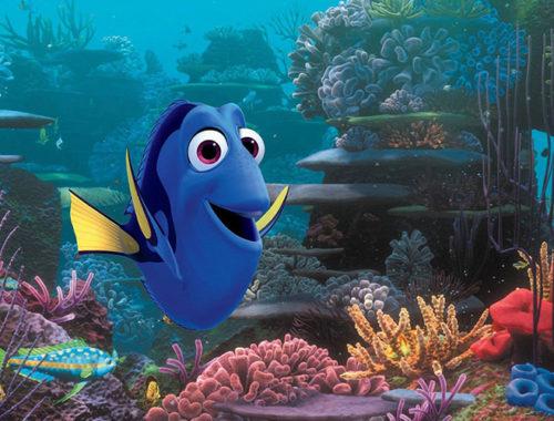 Imagem da Dory, personagem do filme Procurando Nemo e Procurando Dory. Desenho de um peixe azul com nadadeiras amarelas sorrindo no fundo do mar.