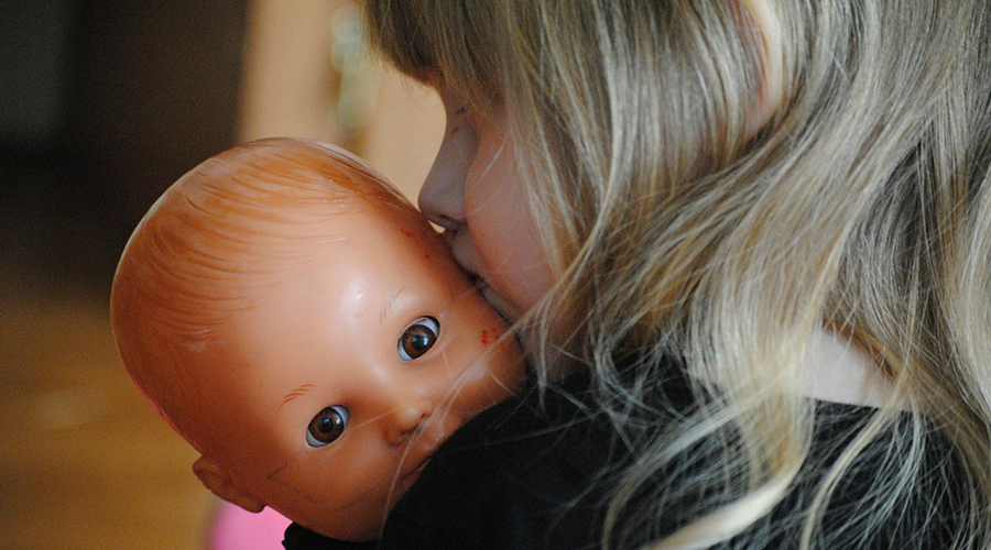 Menina de costas segurando uma boneca de brinquedo e a beijando na cabeça.