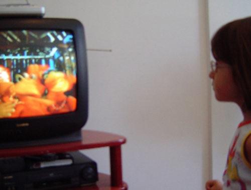 Menina assistindo Cocoricó na TV.