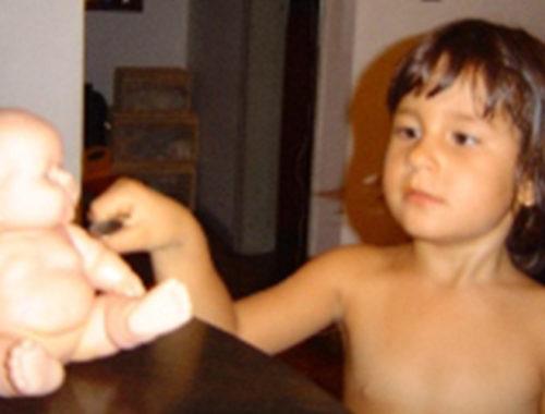 Menina tocando uma boneca de brinquedo em cima da mesa.