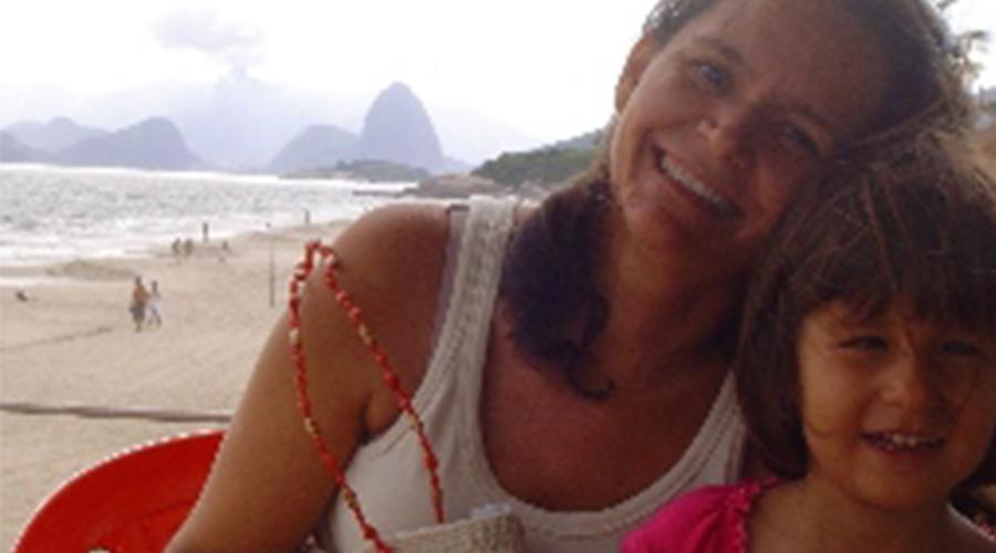 Mãe e filha sorrindo na praia.