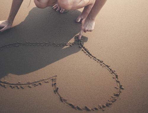 Mão desenhando um coração na areia.