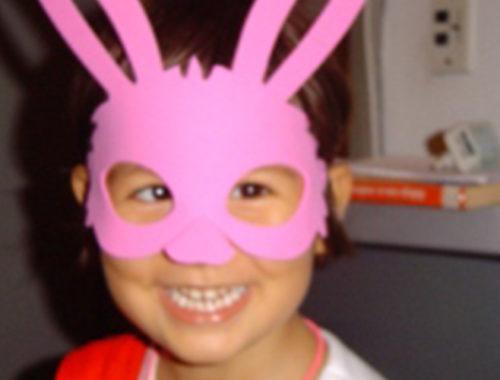 Menina com uma máscara rosa de coelhinho da Páscoa.