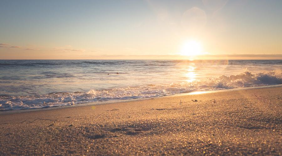 Foto de uma praia ao pôr-do-sol.