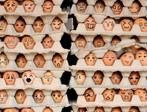 Caixas de ovos dispostas uma sob as outras. Nos ovos estão desenhadas diversas rostos e expressões diferentes.