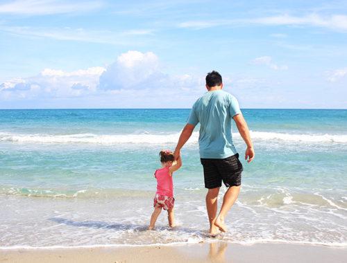 Pai segurando a mão da filha pequena na beira do mar, ambos estão de costas.