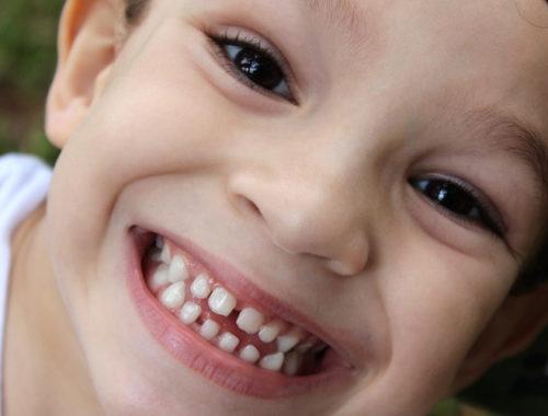 Criança sorrindo para a câmera.