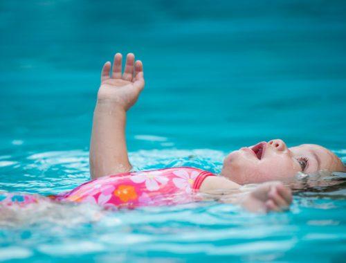 Criança com maiô rosa boiando em uma piscina.