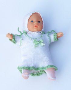 Boneca bebê com roupa de tricô branca em um fundo azul claro.