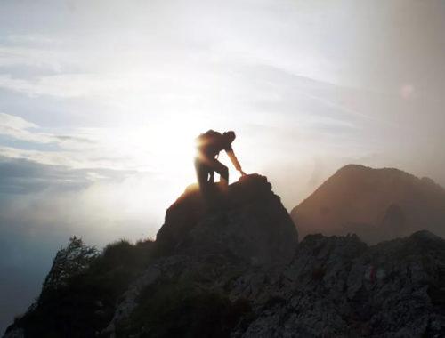Pessoa chegando ao topo de uma montanha com o sol ao fundo.