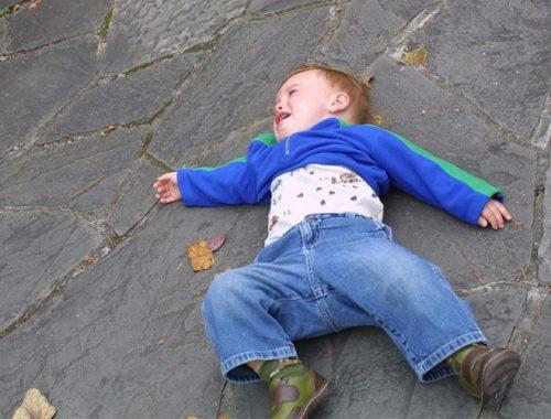 Menino de calça jeans e jaqueta azul atirado na calçada de pedra fazendo birra.