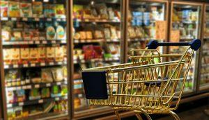Carrinho de supermercado com prateleiras ao fundo.