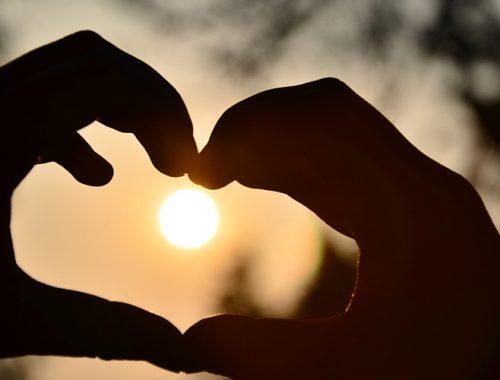 Duas mãos formando um coração com o sol ao fundo.