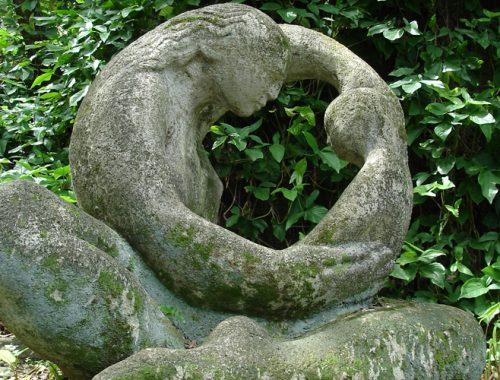Imagem de uma escultura de uma mãe segurando no colo a filha.
