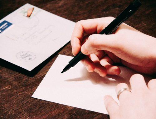 Mão segurando uma caneta e apoiada sob uma mesa e uma folha de papel em branco.