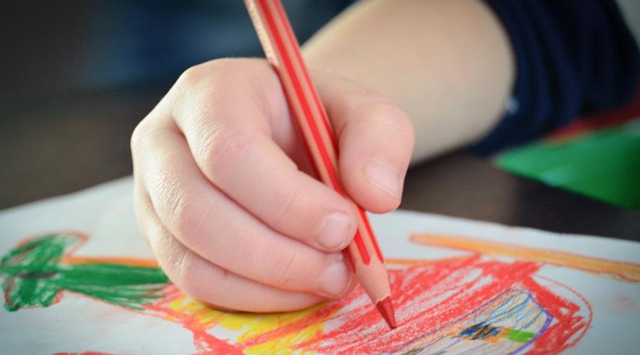 Mão de uma criança segurando um lápis de cor vermelho e pintando um desenho.