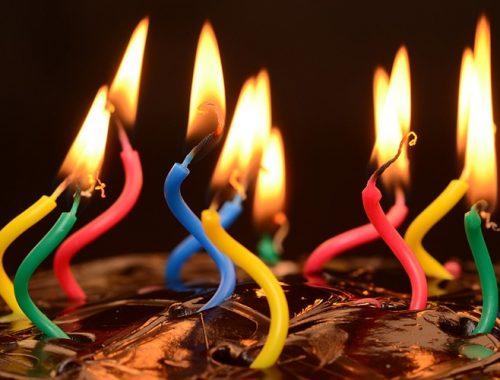 Velas de aniversário acessas em cima do bolo.