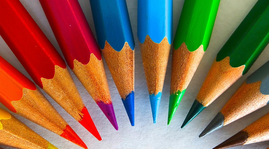 Diversos lápis de cor formando um arco-íris.