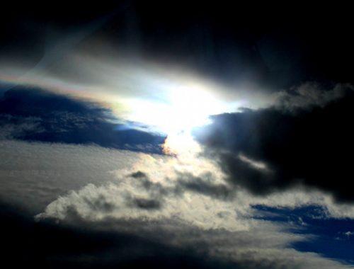 Imagem do céu com o sol saindo por entre as nuvens.