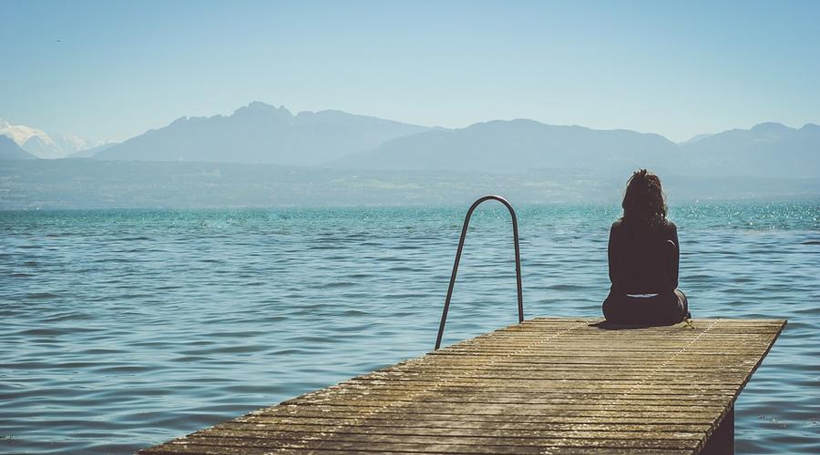 Menina de costas sentada na ponta de um píer.