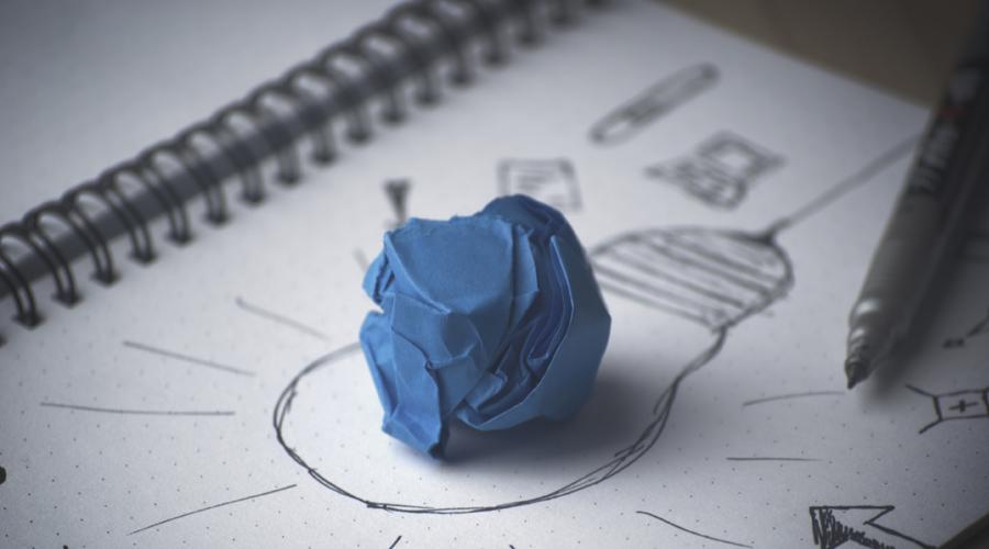 Papel azul amassado feito bolinha em cima de um papel branco com um desenho de uma lâmpada.