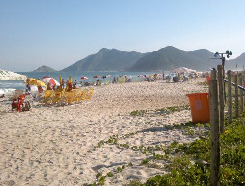 Imagem da beira de uma praia com montanhas ao fundo.