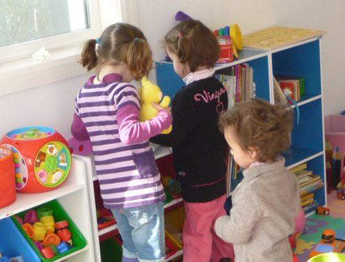 Três crianças pequenas de costas escolhem o brinquedo que vão brincar.