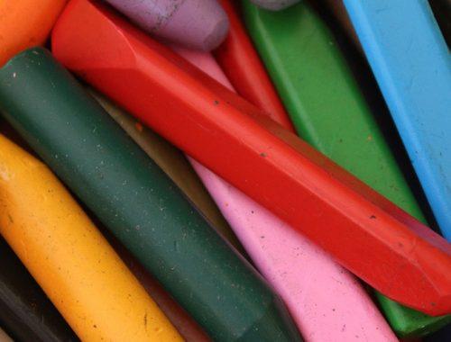 Diversos lápis de giz de cera um em cima do outro.
