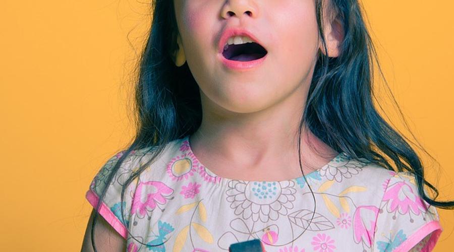 Menina de cabelos compridos com a boca aberta.