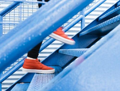 Foto lateral de pés calçados com tênis vermelho subindo uma escada azul.