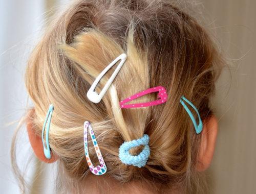 Uma criança de costas com o cabelo cheio de prendedores coloridos.
