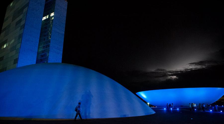 Congresso nacional em Brasília iluminado de azul.