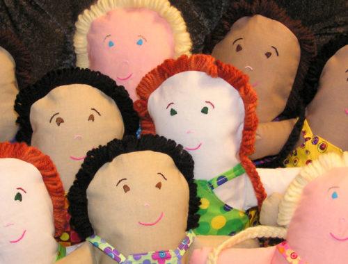 Bonecas de pano de diferentes tons de pele, olhos e cabelo.