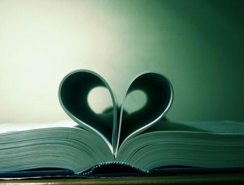 Livro aberto sob a mesa com as páginas dobradas formando um coração.