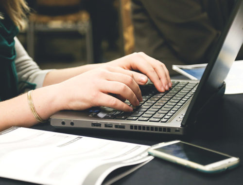 Foto de mãos de uma mulher digitando em um notebook.