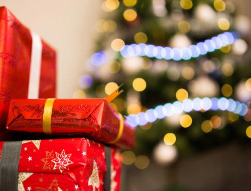 Foto de três presentes de pacotes vermelhos empilhados e, ao fundo, uma árvore de Natal com luzes azuis.
