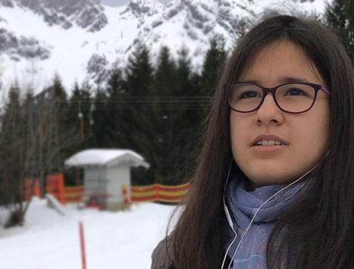 Foto do rosto de uma menina de frente com montanhas de neve ao fundo.