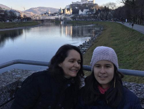 Duas mulheres posam para a câmera e no segundo plano se vê um lago e pessoas caminhando.